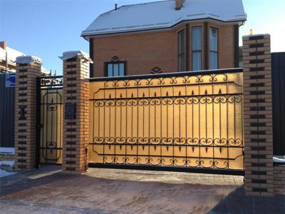 Откатные ворота сварные, с элементами ковки зашитые поликарбонатом. Установлены на кирпичные столбы.